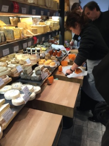 Slicing and preparing cheese in a Parisian fromagerie.